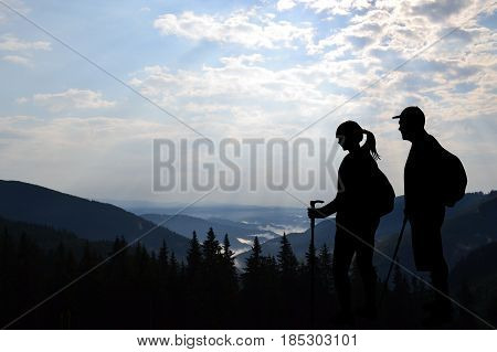 Couple of tourists enjoying valley view from top of a mountain