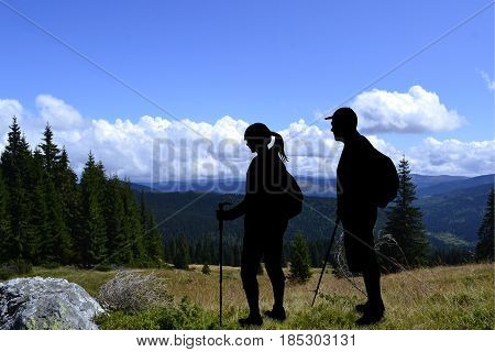 Couple of tourists hiking in mountains landscape