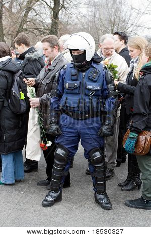 RIGA, LATVIA - MARCH 16: Local police guards the crowd at the Freedom Monument during Commemoration of the Latvian Waffen SS unit on March 16, 2009 at Riga, Latvia.