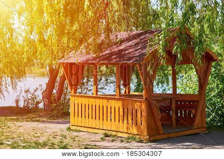 Gazebo For Family Entertainment And Is Made Of Wood, Stands On The Shore Of The Lake