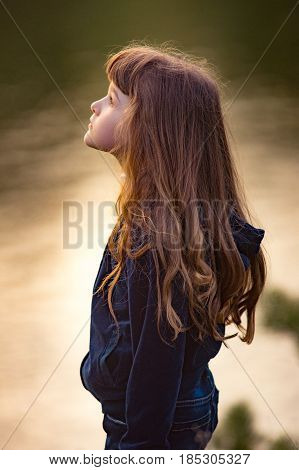Young teen brunette girl with tears in her eyes with long hair standing Against the water background. Sadness resentment disappointment and despair