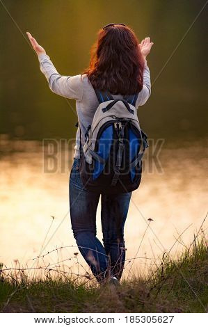 Young woman stands with raised arms up to the sun on the nature background. Travel Freedom Lifestyle concept.