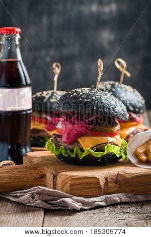Gourmet black burger with berry sauce, and drink on wooden table and dark background