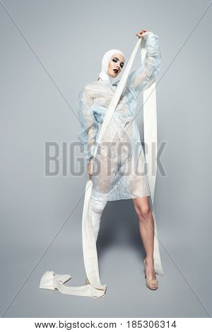 Fashion shot. Gorgeous female model in bandages and hospital gown posing at studio with crutches. Beauty and medicine, plastic surgery.