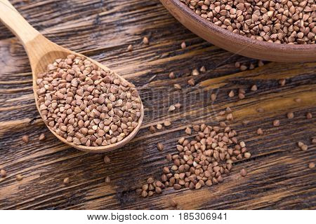 standing on a wooden background earthenware dish with raw buckwheat