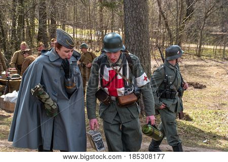 Gatchina Russia - May 7 2017: Historical reconstruction of the battles of World War II. Participants in the reconstruction. In the foreground are German soldiers of the communications and sanitary service.
