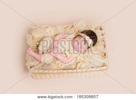 Relaxed baby girl in pastel yellow outfit napping in the child's basket, topview poster