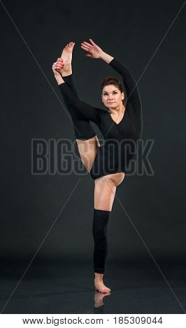 Sporty dancing girl on black background and holds up one feet while stretching