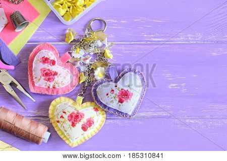 Cute hearts keychain with flowers beads. Hand felt and fabric keychain on bag or backpack. Summer accessorize for women or girls. Crafts concept. Wooden background with copy space for text. Top view
