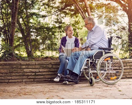 Disabled grandfather in wheelchair in park spending time together with his granddaughter reading book outdoor