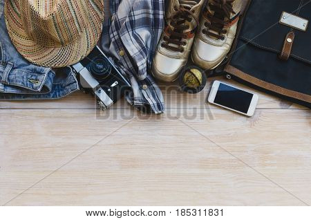 Top view of traveler´s accessories: leather bag blue jeans hat check shirt gold sneakers smart phone vintage camera and globe on wooden background with space for text. Travel outfit concept.