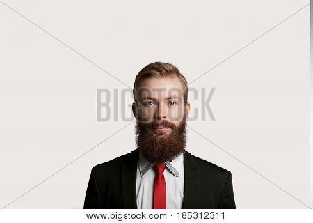 Handsome bearded top manager in black suit and red tie. Quiet emotion on man face. Guy keep tranquility and look to the camera. Big boss have speech for customers about big sale.