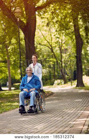 elderly man on wheelchair with caregiver nurse outdoor