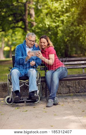 daughter with her disabled father in wheelchair using a digital tablet, talking and smiling while spending time in the park