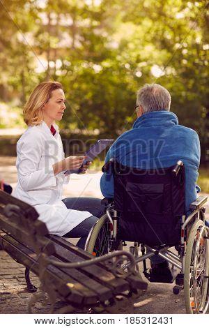 nurse checking up the history of the patient in wheelchair
