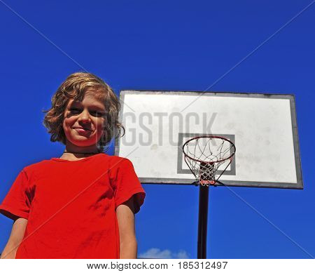 Happy smiling boy with the basketball hoop on background