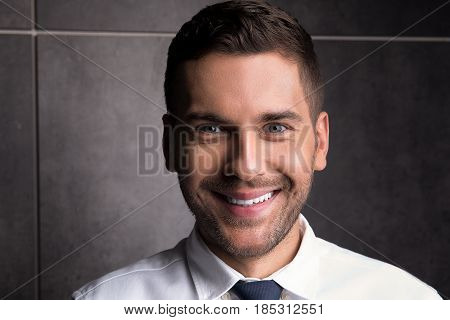 Just be happy. Portrait of youthful successful businessman. He is looking at camera merrily
