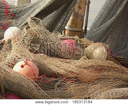 A pile of old fishing nets with hollow round plastic floats