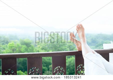 Relax Feet Of Young Woman Lying On Soft Mattress.