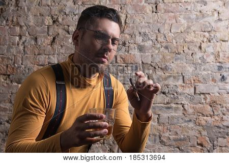Melancholy mood. Portrait of trendy man sitting with glass and cigarette and looking down. Brick wall in the background