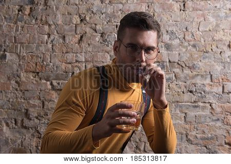 Bad habits. Portrait of youthful modern man sitting against brick wall smoking and drinking. He looking at camera intently