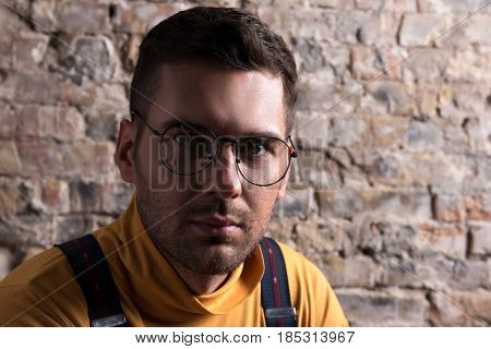 Loneliness. Portrait of youthful elegant man in glasses. He looking at camera thoughtfully