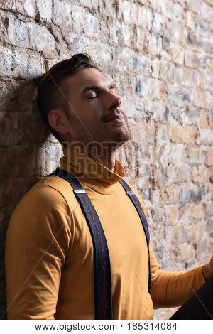 Dreamy man. Calm young guy with closed eyes. He leaning against brick wall with smile