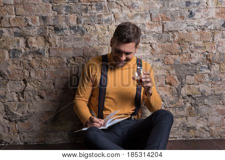 Notes of happy man. Cheerful young guy doing notes while drinking and sitting on wooden floor. He looking at notebook