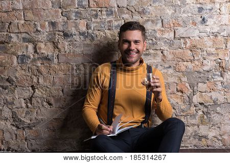 Insouciance. Cheerful young man sitting with notebook and glass. He looking at camera and laughing