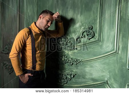 Dreams of you. Young guy with closed eyes leaning onto wall and relaxing. He holding one hand in his pocket and the other one at his hand