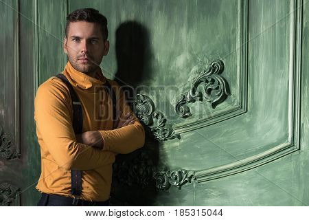 Time for change. Waist up portrait of serious guy looking at camera with concentration. He standing with crossed arms. Copy space