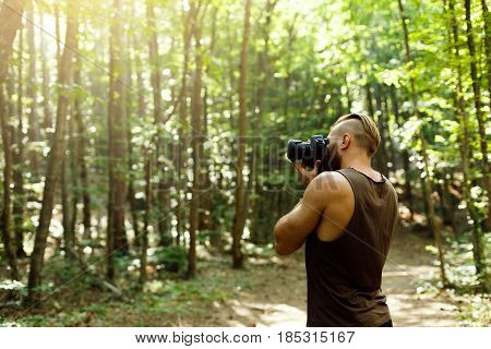 Bearded photographer man trekking among forest and taking pictures with dslr camera. Horizontal shape, side view, copy space