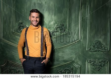 Relax and take it easy. Young trendy man leaning against green wall. His hands in his pockets. He wearing orange polo neck, suspenders and black pants