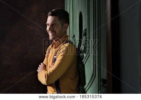 Enigmatic smile. Charming young man leaning against wall. He looking aside positively. His arms are crossed