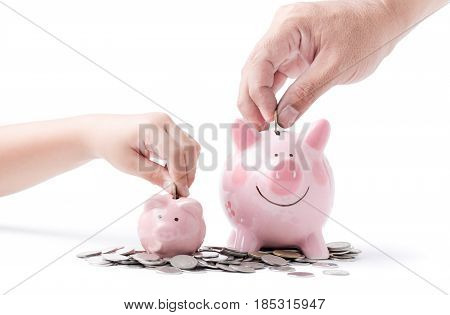 Father And Child Hand Put Coin To Piggy Bank Isolated