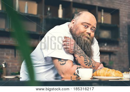 Portrait of happy male fatso having breakfast in kitchen. He is looking at camera and gently smiling. Cup of coffee and croissant on table