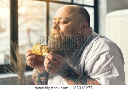 What wonderful smell. Fat bearded guy is enjoying scent of fresh baked pastry. His eyes are closed with pleasure