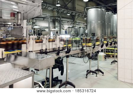 Plastic bottles with beer on the conveyor. Brewing production.