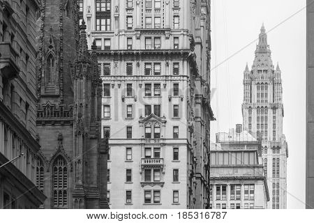 New York City, Lower Manhattan, arhitectural detail of Broadway street wiev: Trinity Church, New York City Charter School Center and Woolworth building far away. Black and white vintage image.