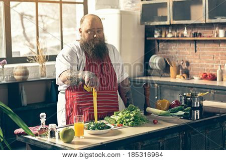 Lazy fat man is standing in kitchen and holding knife with unwillingness to cook. Abundance of vegetables on table