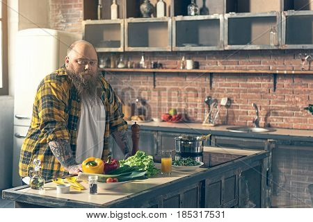 I am very hungry. Irritated fat man is standing in kitchen near fresh vegetables on table. He is looking at camera with dissatisfaction