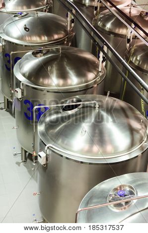 Several glossy steel cylindrical tanks with semicircular covers. Glossy and clean surface of stainless steel.