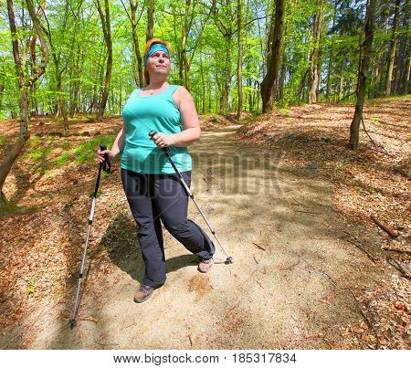 Overweight woman walking on forest trail. Slimming and active lifestyle theme.