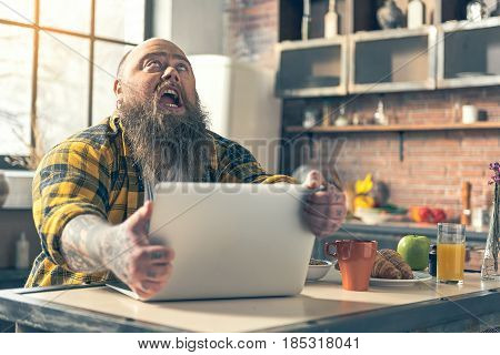 Irritated fat man is suffering from hunger. He is holding his laptop with aggression and shouting. Guy is sitting in kitchen