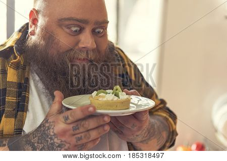 Starving fat man is staring at sweet dessert with appetite. He is standing and holding plate