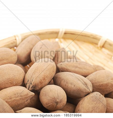Close-up fragment of a wicker basket full of pecan nuts isolated over the white background