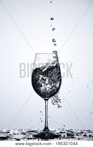 Water splash and bubbles in wineglass standing on the glass with water splashing against light background. Natural and environmentally product. Drinking and useful water. Concept of the healthy lifestyle.