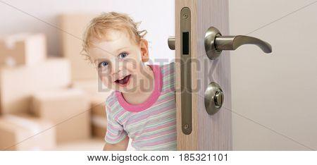 happy kid behind door in new room