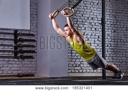 Young athlete man working out in gym pull ups with gymnastic rings against brick wall in the cross fit gym. Sportsman in the sportwear, t-shirt, shorts and sportive shoes. Concept of the cross fit activity.
