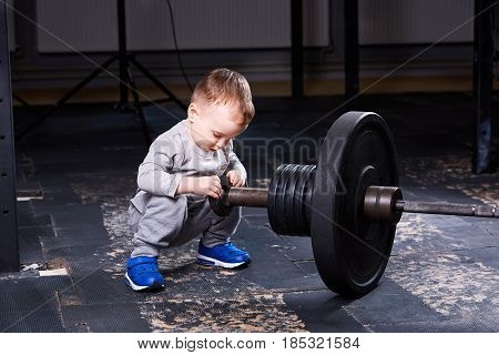 Cute little boy with dumbbells in the cross fit gym. Sporty child in the grey sportwear and blue sportive shoes. Concept of the rearing children in the healthy lifestyle.